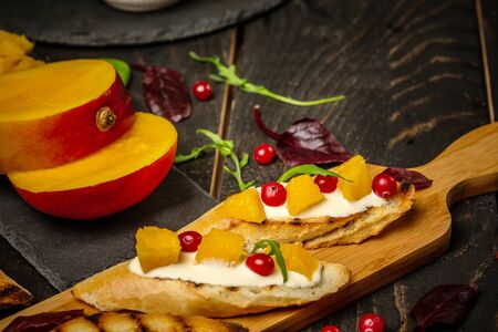 Bruschetta with sweet mango, pomegranate cheese. on wooden background. Healthy food, Flat top view. 写真素材