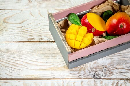 Famous Alphonso mango slices in a wooden box, wood background, Top view. Free copy space.