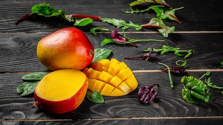 Mango tropical fruit on a dark wooden background. Flat lay. place for text. Food concept.
