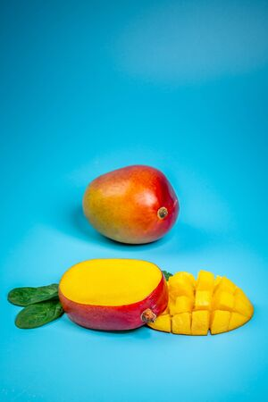 Fresh mango organic product, tropical fruit. blue background. Top view. Copy space vertical image.