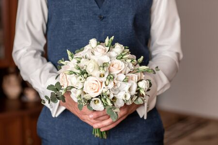 Beautiful man in a suit holding hands delicate flowers. Gift to Womens Day. Agency floral design. Gift bouquet on March 8. groom preparing for the wedding.