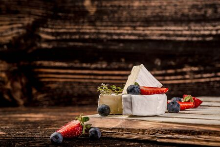 French delicacy. Elegant Camembert. Soft cheese with white mold with wild berries. Round Camembert with strawberries and blueberries. Healthy and tasty Breakfast