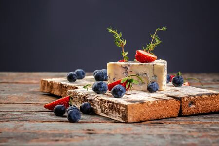 Roquefort, French blue cheese with mold on a wooden surface, served with blueberry and strawberry