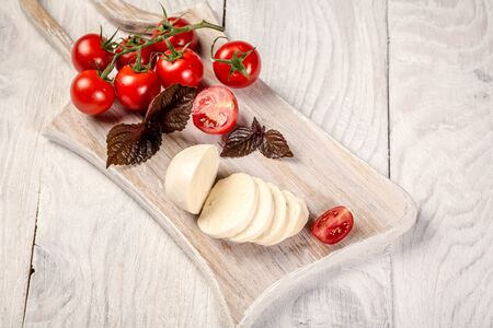Mozzarella cheese, basil and tomato cherry on slate stone board, copy space. Ingredients for Caprese salad. Free space for your text