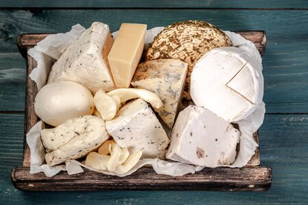 various types of cheese on rustic wooden table in box.