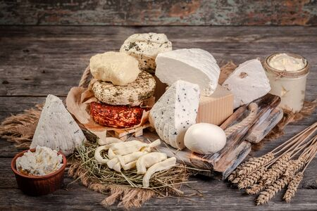 A large variety of cheeses on rustic background.