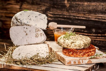Different sorts of cheese on wooden table. Rustic Style Goat Cheese. space for text.
