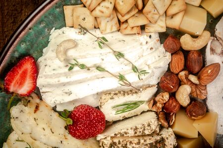 Cheese plate served with blueberry, strawberry, crackers and nuts, Top view. Assorted cheeses Camembert, Brie, Parmesan blue cheese, goat.