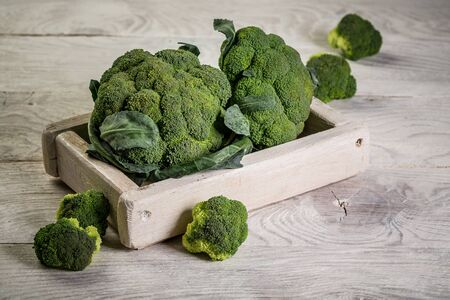 Raw broccoli on wooden background. Broccoli vegetable is full of vitamin. Vegetables for diet and healthy eating. Organic food.