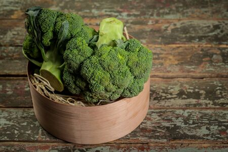 Fresh broccoli in bowl on wooden table close up. Organic food.