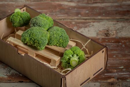 Fresh green broccoli in wood bowl over rustic wooden background healthy or vegetarian food concept Top view.