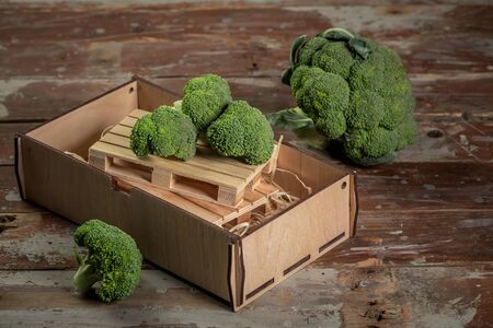 Bunch of fresh green broccoli on brown plate over wooden background. Top view. Free copy space.