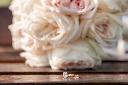 Close up bouquet of roses of pastel shades. A ring near the flowers.