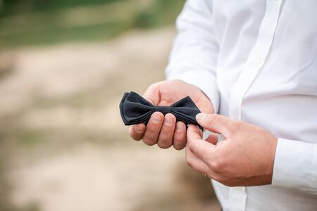 close up of mans hand holding tie butterfly. close up of groom getting ready. grooms morning.Bow tie in the hands of the groom.