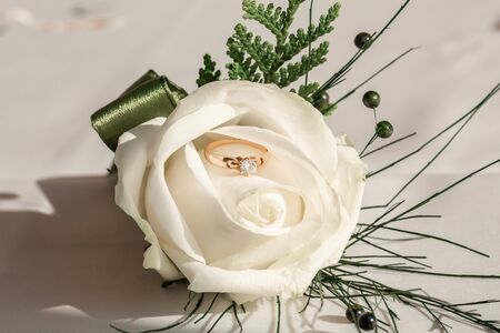 Close-up picture of wedding boutonniere with wedding ring. Wedding accessories bride and groom. Reklamní fotografie