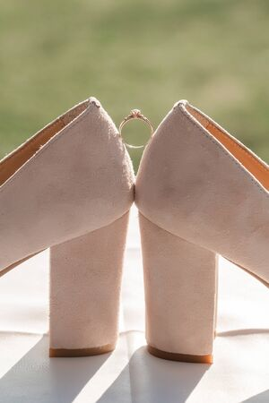 Gold wedding ring with womens shoes on the wedding day. Bridal accessories for wedding day. Reklamní fotografie