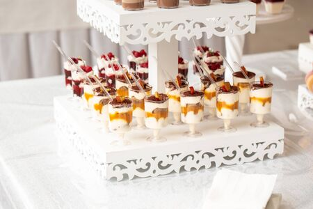 luxury wedding catering, table with modern desserts, cupcakes, sweets with fruits. delicious candy bar at expensive wedding reception. space for text. Dessert table for a party.