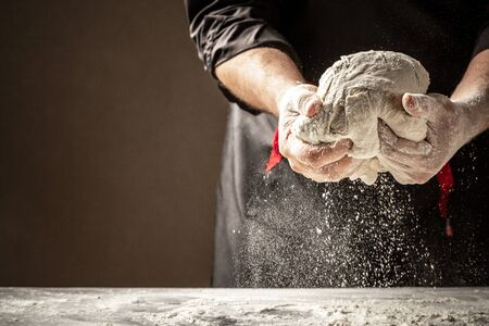 male kneading dough on table, closeup. Preparation of Easter bread.Men hands.