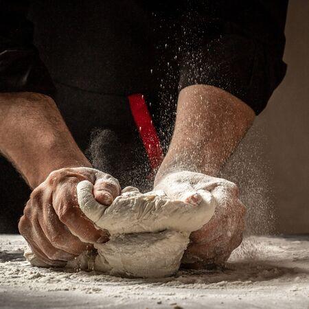 Homme préparant la pâte à pain sur une table en bois dans une boulangerie se bouchent. Préparation du pain de Pâques. Mains d'hommes.