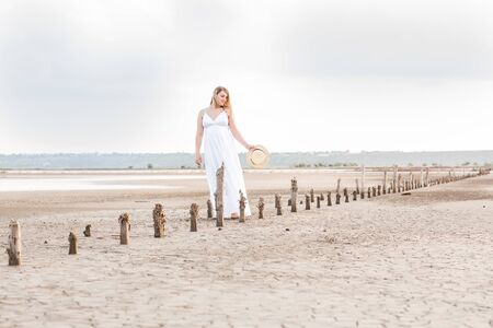Portrait of a beautiful pregnant blonde woman in a white dress on a desert background. wind and summer sun.abandoned salt production. Happiness of motherhood, expectation.