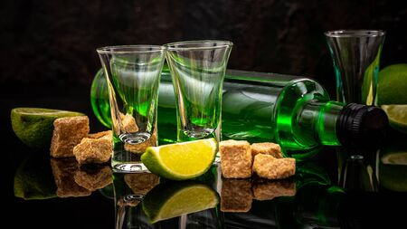 green cocktail on the basis of absinthe in a stylish vintage glass. absinthe in glass with lime slices on dark background 版權商用圖片