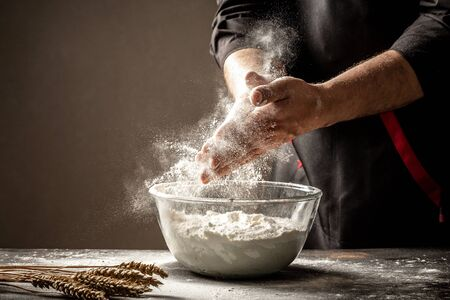 Hand clap of professional chef with bowl for cooking and baking utensils with splash flour on dark background. Empty space for text.