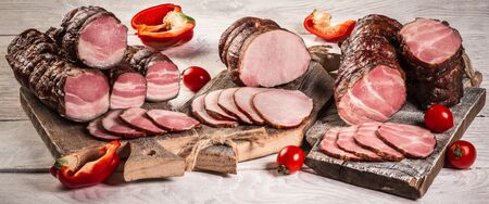 Set sliced smoked gammon on a wooden table with fresh herbs and aromatic spices. Natural product from organic farm. banner. Stock Photo