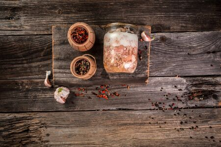 Canned meat in a glass jar on a wooden table. farm organic food. banner menu recipe place for text.