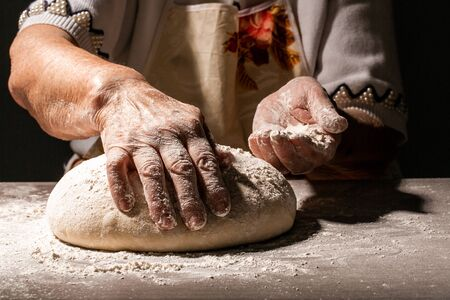 Preparing traditional homemade bread. Close up view of old woman, grandmother kneading dough. Homemade bread. Hands preparing bread dough on wooden table.