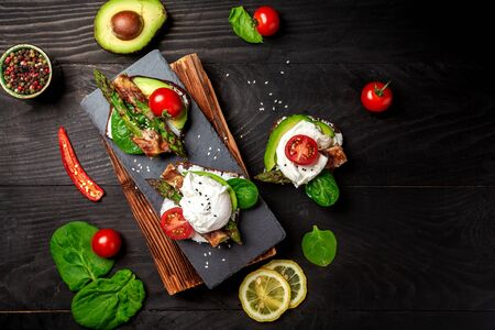 Italian food: snack toasts with avocado, asparagus and fried egg, top view. Food recipe background. Zdjęcie Seryjne