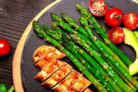 Baked chicken garnished with asparagus and herbs. Healthy food, ketogenic diet, diet lunch concept. Keto Paleo diet menu. Top view, overhead. Foto de archivo