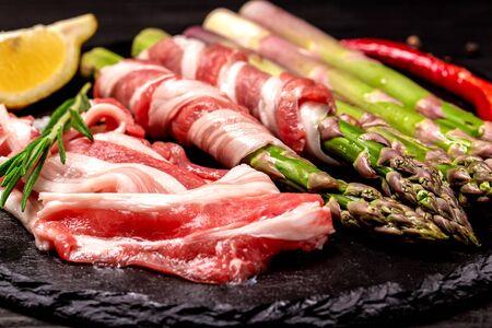 Gros plan d'asperges enveloppées de bacon. Planche de schiste d'ingrédients crus préparée pour la torréfaction ou la friture.