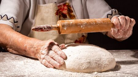 Beautiful and old women's hands knead the dough from which they will then make bread, pasta or pizza. A cloud of flour flies around like dust. Food concept Banco de Imagens
