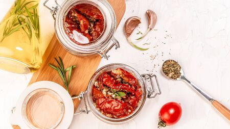 tomato dried tomatoes, dried tomatoes in jar, basil, and herbs in spoon on a light table. top view. Long banner format. space for text.