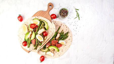 Stack whole grain tortillas. Ingredients for Flatbread Paratha roti cherry tomatoes, asparagus, on light gray background. Top view. Long banner format. space for text.