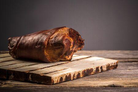 Smoked pork knuckle, rustic wooden background. Natural farm food. Big smoked pork knuckle, Bavarian grilled knuckel of pork - German Pork Hocks. space for text. Standard-Bild