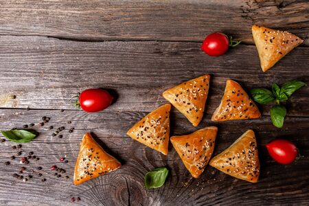 Samsa or samosas with meat and vegetables on rustic background, top view. Traditional Indian food. Copy text.