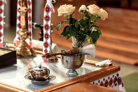 The Sacrament of Baptism. Attributes of the Orthodox priest for baptism, the cross, baptism holy water and candle. Catholic baptism.