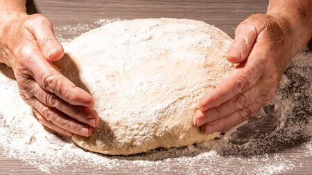 Female hands kneading fresh dough. Preparing homemade dough. Cooking with love concept. Top view. Stock Photo