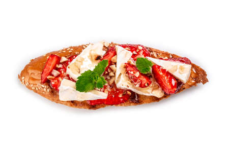 Crostini with strawberries, cheese camembert, nuts and honey isolated on a white background. top view 写真素材