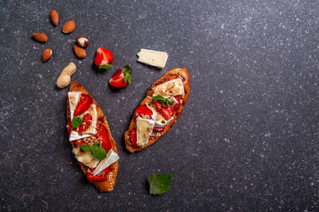 Crostini with strawberries, cheese camembert, nuts and honey. top view