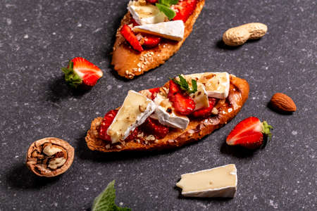 Summer snack. Delicious homemade Bruschetta strawberry toast ciabatta, cheese camembert nuts and honey. Food recipe background. space for text. top view