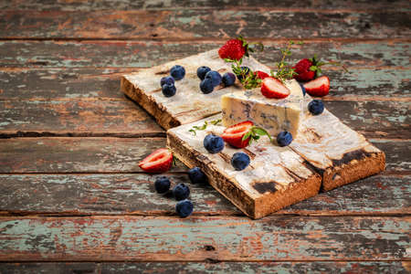 Blue and brie cheese. On a wooden background. served with blueberry and strawberry. The concept of eco products. Background image. Copy space.