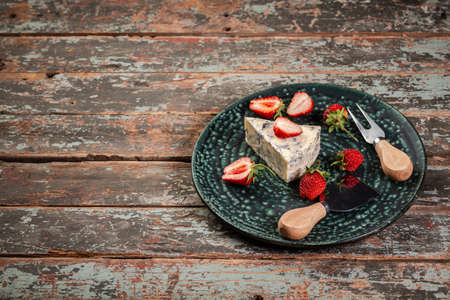 Blue and brie cheese. served with strawberry. The concept of eco products. Background image. Copy space.