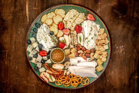 Cheese plate with different types of cheese with honey and nuts. Sliced pieces of various cheese on a wooden table. Rustic background.
