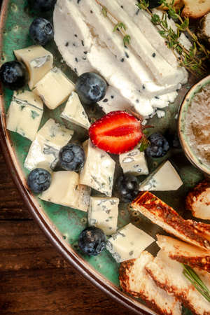 Cheese plate with different types of cheese with honey and nuts, blueberries and strawberries. free space for text. 写真素材