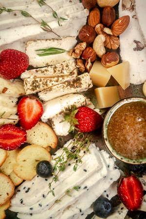 Cheese plate with different types of cheese with honey and nuts, blueberries and strawberries. 写真素材