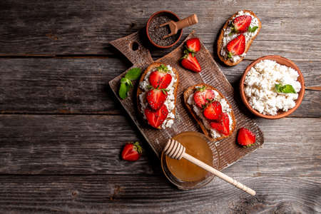 bruschetta with whole grain bread, cottage cheese, strawberry, honey. catering banner menu recipe place for text, top view.