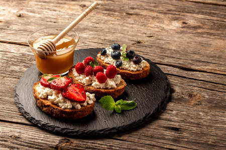 Bruschetta or toast with goat cheese, berries and honey. Food recipe background. Close up top view. 스톡 콘텐츠