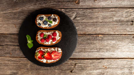 Assortment of fruit toasts with ricotta on stone background. banner, catering menu recipe place for text, top view. 写真素材